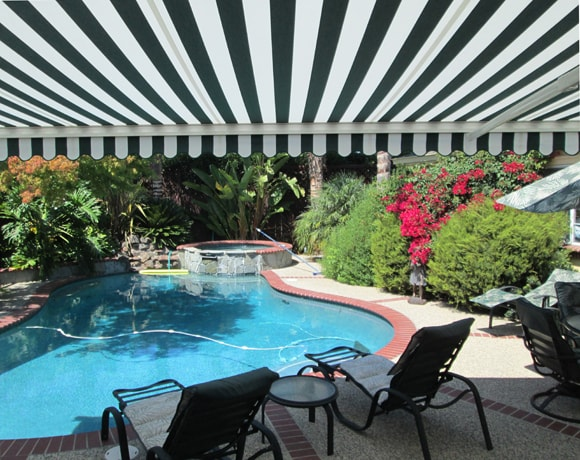 This Green And White Striped Motorized Retractable Awning In San Jose Creates A Comfortable Shaded Backyard Installed By European Rolling Shutters